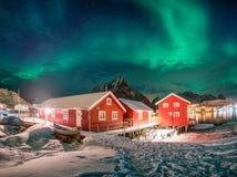 Rood huis in de visserij van dorp met aurora borealis over noordpooloc royalty-vrije stock foto's