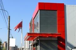 Rood huis met glasvensters, verkoopbureau dichtbij de weg stock afbeelding