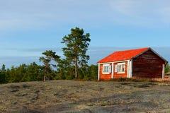 Rood huis op de rots Stock Fotografie