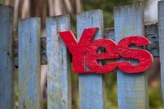 Rood 'ja' op een blauwe houten poort Stock Afbeeldingen