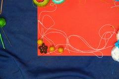 Rood kader met verwarring van het breien van draden op blauwe achtergrond Stock Foto's