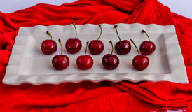 Rood kersenfruit op een witte porcelan plaat Stock Foto