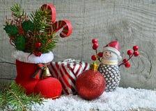 Rood Kerstman` s laars, spar, gift, sneeuwmanbeeldje en Kerstmisbal op houten achtergrond De achtergrond van Kerstmis Stock Foto's