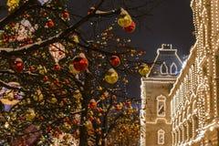 Rood Kerstmisspeelgoed die op de bomen tegen de achtergrond hangen stock foto