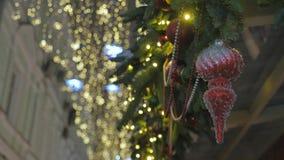 Rood Kerstmisspeelgoed die op de takken van sparren hangen Op de achtergrond, uit nadruk is de gele feestelijke verlichting stock footage