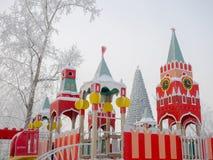 Rood kinderen` s dorp in de vorm van de toren van het Kremlin op de achtergrond van de Kerstboom in het stadspark Stock Foto's