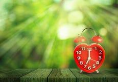 Rood klokteken op de klok van 7 o ` gezet op houten tafelblad Stock Afbeelding