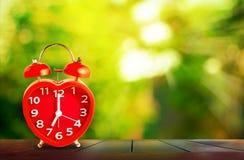 Rood klokteken op de klok van 7 o ` gezet op houten tafelblad Stock Afbeeldingen