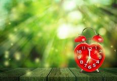 Rood klokteken op de klok van 7 o ` gezet op houten tafelblad Stock Fotografie