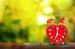Rood klokteken op de klok van 7 o ` gezet op houten tafelblad Royalty-vrije Stock Afbeeldingen