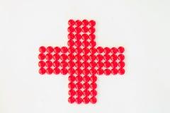Rood kruis dat met rode pillen wordt gemaakt Stock Foto's