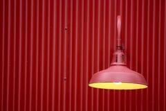 Rood licht tegen rode metaalachtergrond Stock Afbeeldingen