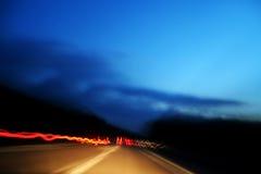 Rood lichten die van snelle auto in weg worden gemaakt Stock Fotografie