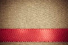 Rood lint op bruine stoffenachtergrond met exemplaarruimte. Stock Afbeeldingen