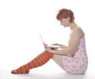 Rood Meisje in streepsokken met laptop Royalty-vrije Stock Fotografie