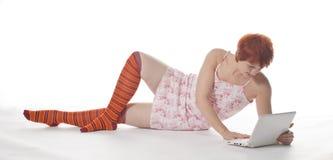 Rood Meisje in streepsokken met laptop Royalty-vrije Stock Foto's