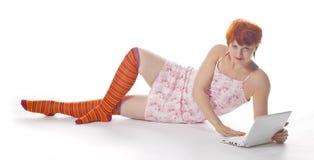 Rood Meisje in streepsokken met laptop Stock Foto's