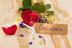 Rood nam bloem en markering met Duitse woord, Gutschein, middelenbon of coupon toe stock afbeelding