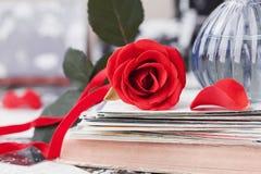 Rood nam bloem met een stapel van prentbriefkaar, retro foto's en uitstekend boek toe Stock Afbeeldingen