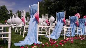 Rood nam bloemblaadjes voor huwelijksceremonie in het open platteland, de zomer, warm weer, Chiavari-stoelen toe stock video