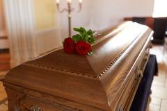 Rood nam bloemen op houten doodskist in kerk toe stock fotografie