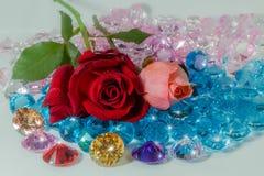 rood nam toe en het roze nam bloemen is op de kleurrijke halfedelstenen toe Royalty-vrije Stock Afbeeldingen