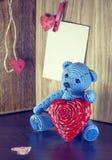 Rood nam toe Teddy Bear Loving leuk met rode harten die alleen zitten wijnoogst stock foto's