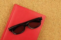 Rood notitieboekje en zwarte glases op de cork raad Royalty-vrije Stock Afbeeldingen