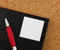 Rood notitieboekje en zwarte glases op de cork raad Stock Afbeeldingen