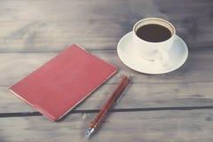Rood notitieboekje met pen en koffie Stock Afbeeldingen