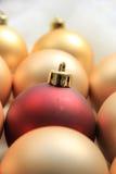 Rood ornament op een stapel van gouden ornamenten Royalty-vrije Stock Afbeeldingen