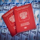 Rood paspoort twee op de achtergrond van honderd dollarsrekeningen Blauw ontwerp stock foto's