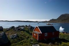 Rood plattelandshuisje in Groenland met witte ijsberg Stock Afbeeldingen