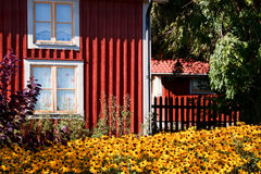 Rood plattelandshuisje met buiten bloem. Royalty-vrije Stock Afbeelding