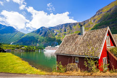 Rood plattelandshuisje tegen cruiseschip in fjord, Flam, Noorwegen stock afbeelding