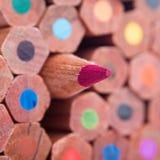 Rood potlood die van de menigte duidelijk uitkomen stock afbeelding