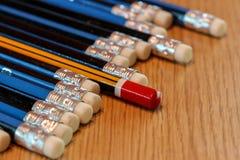 Rood potlood die van menigte van blauwe potloden op houten lusje duidelijk uitkomen Stock Afbeeldingen