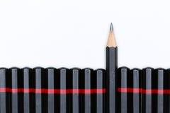 Rood potlood die van menigte van overvloeds identieke kameraden duidelijk uitkomen stock afbeeldingen