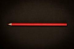 Rood potlood op zwart document royalty-vrije stock afbeelding