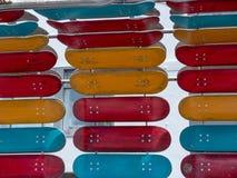 Rood, sinaasappel, en de dekken van het wintertalingsskateboard opgezet op een installatio royalty-vrije stock fotografie
