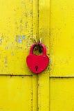 Rood slot op een roestige gele deur stock afbeeldingen