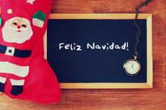 Rood sok en bord met feliz navidad groet Vakantieachtergrond met spar en groettekst Stock Afbeelding