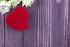 Rood stoffenhart met bloemen op de donkere houten achtergrond De dag van de valentijnskaart Huwelijk De kaart van de groet Stock Foto's