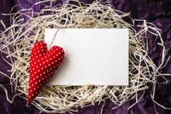 Rood stuk speelgoed hart en lege kaart op stro Royalty-vrije Stock Foto's