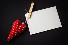 Rood stuk speelgoed hart en lege kaart op zwarte Royalty-vrije Stock Fotografie
