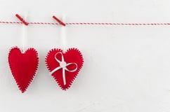 Rood twee voelde harten die op de kabel vast die door wasknijpers hangen op witte achtergrond worden geïsoleerd Het concept van d royalty-vrije stock fotografie