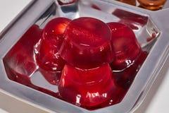 Rood van de geleiaardbei en kers suikergoed op een macro van de metaalplaat Stock Foto's