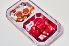 Rood van de geleiaardbei en kers suikergoed op een macro van de metaalplaat Stock Fotografie