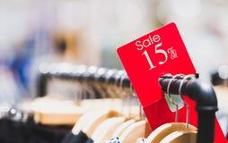 Rood verkoopteken 15% korting op kledingsrek in modern winkelcomplex of warenhuis met exemplaarruimte Stock Afbeelding