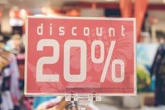 Rood verkoopteken 20 percentenkorting op vage achtergrond in een winkelcomplex van Bali, Indonesië, Azië Stock Afbeelding